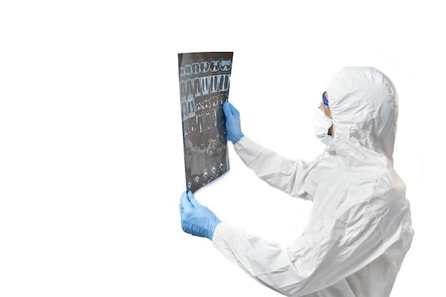 Un medico con una tuta protettiva e una maschera esamina i risultati di una tac dei polmoni per rilevare il coronavirus.