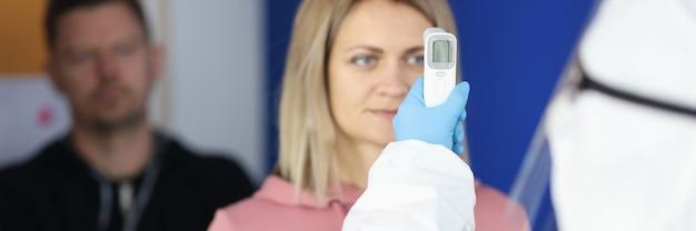 Il dottore in tuta protettiva misura la temperatura dei visitatori.