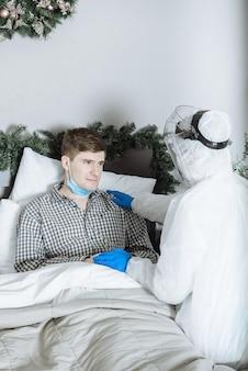 Un medico in tuta protettiva ppe hazmat esamina un paziente malato con coronavirus covid-19