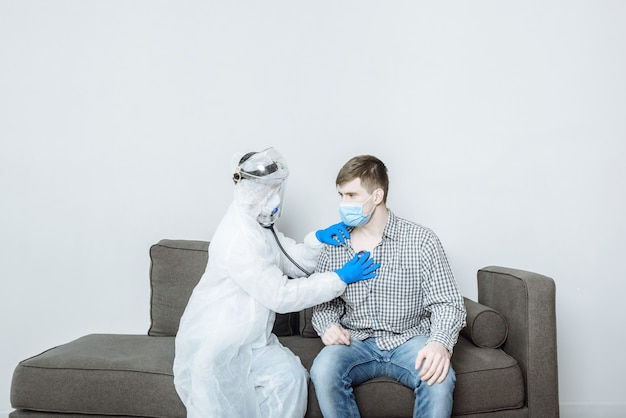 Un medico in una tuta protettiva ppe hazmat in una maschera e guanti esamina il paziente e ascolta con uno stetoscopio per respirare