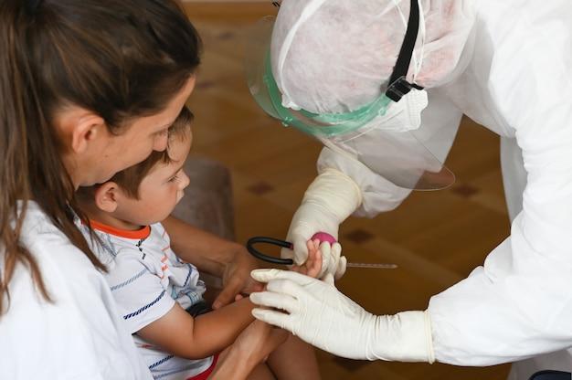 Un medico in una tuta protettiva esegue un esame del sangue da un bambino a casa