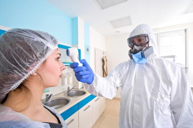 Medico in divisa e maschera protettiva che controlla la temperatura del giovane paziente femminile.