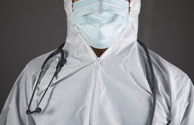 Dottore in uniforme protettiva e con uno stetoscopio su una scena grigia