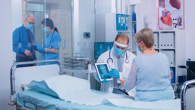 Medico in visiera protettiva che parla con il paziente che indossa una maschera che spiega il risultato dei raggi x su tablet pc digitale in una moderna clinica privata o ospedale. roba medica che funziona dopo l'epidemia di coronavirus