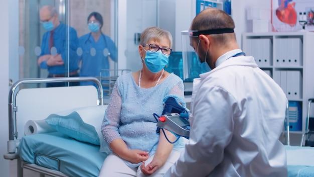Medico in abbigliamento protettivo durante covid-19 che misura la pressione sanguigna della vecchia signora in pensione in ospedale o clinica privata. infermiera che lavora in background, esaminando pazienti, assistenza medica e sistema sanitario