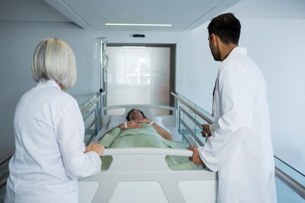 Medico che spinge il letto della barella di emergenza in corridoio