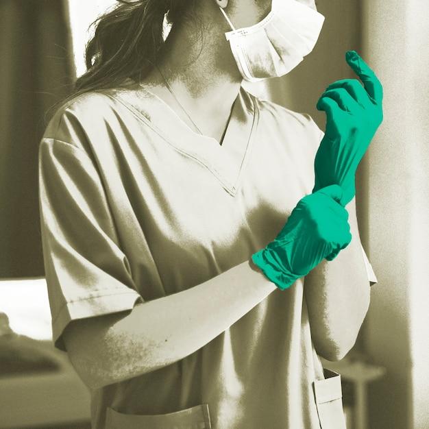 Medico che indossa un guanto per prevenire la contaminazione da coronavirus