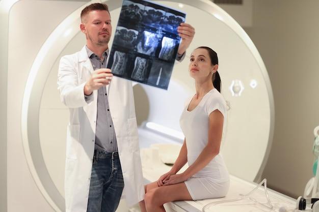 Medico radiologo guardando l'istantanea della colonna vertebrale del paziente davanti all'ernia spinale della macchina per la risonanza magnetica