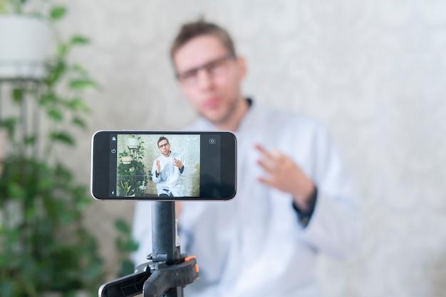 Dottore che legge la lezione agli stdent online usando un telefono come webcam