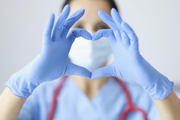 Dottore in guanti di gomma che mostra il cuore con il primo piano delle mani