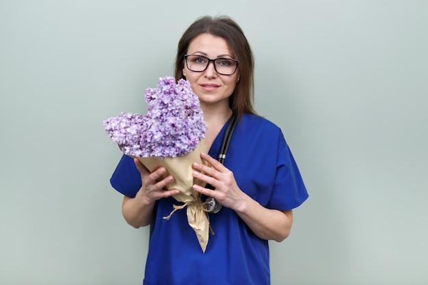 Festa del dottore, celebrazione. medico femminile sorridente felice con il mazzo di fiori, posa femminile che esamina la macchina fotografica, fondo verde chiaro