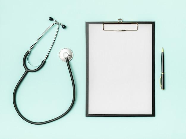 Vista da scrivania del medico. stetoscopio e taccuino su una tavola colorata