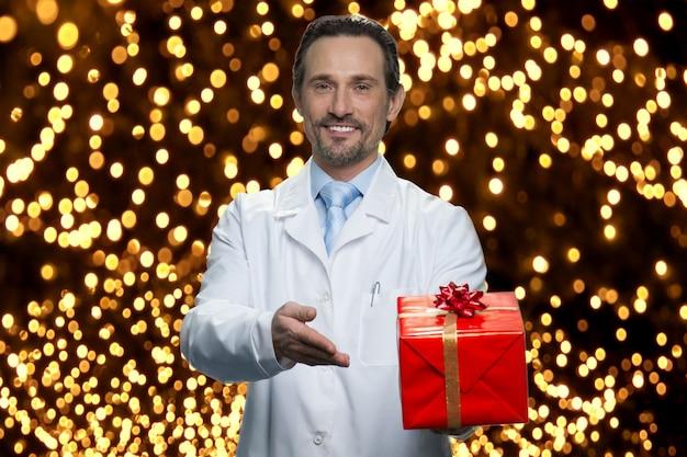 Il dottore ti sta facendo un regalo per natale. indicando la confezione regalo rossa. molte luci incandescenti sullo sfondo.