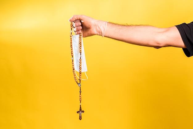La mano del medico tiene una maschera sanitaria accanto a un rosario con una croce cristiana.