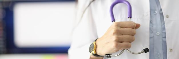 La mano del medico tiene lo stetoscopio in studio medico. concetto di servizi del medico