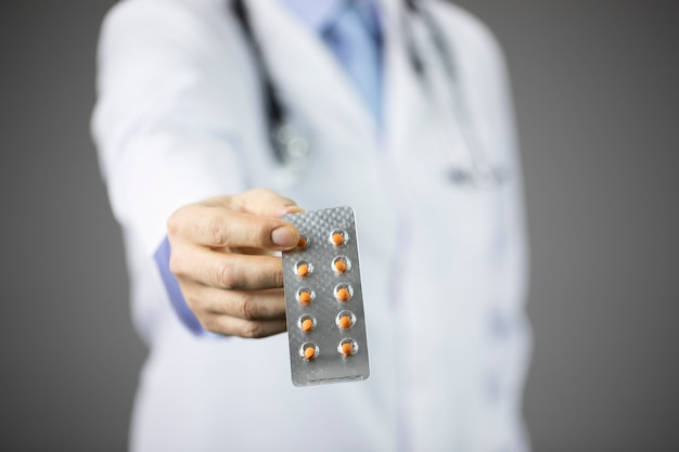 La mano del medico offre pillole di prescrizione in blister isolate sul muro grigio