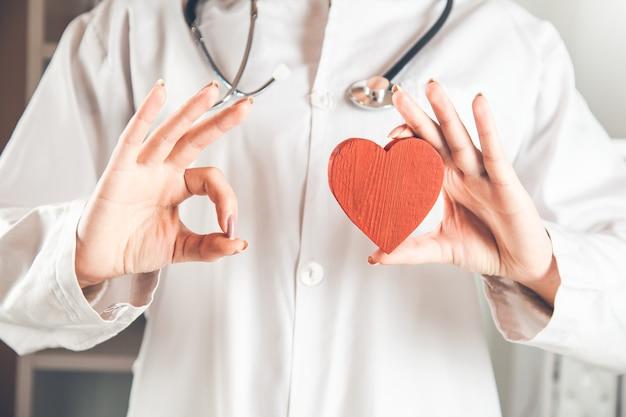 Cuore rosso della mano del medico e segno giusto