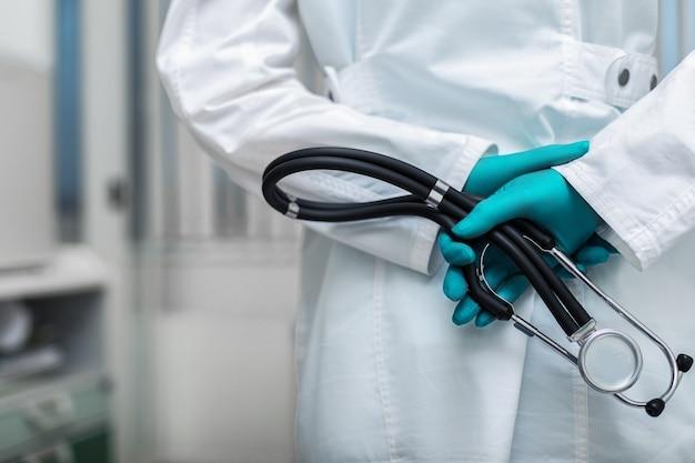 La mano del medico in un primo piano delle camice che tiene un fonendoscopio sullo sfondo di una stanza d'ospedale. copia spazio, concetto di medicina