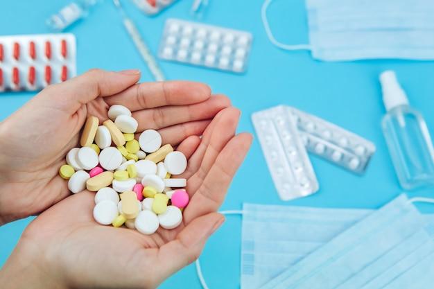 Le mani del dottore tengono in mano delle pillole. cura per coronavirus. rimedi medici nella lotta contro covid-19. pillole, siringhe, termometro, maschera medica sul tavolo blu.