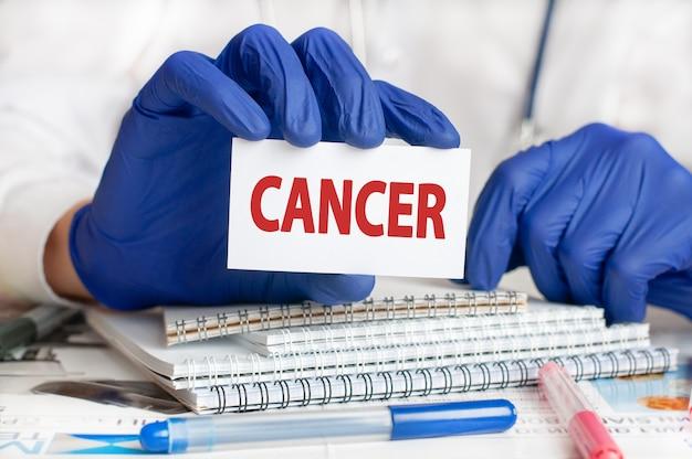 Mani del medico in guanti blu che tengono una carta con il cancro del testo. sul blocco note da tavolo per cartelle cliniche e penne. concetto medico e sanitario. messa a fuoco selettiva.