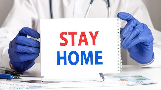 Mani del medico in guanti blu che tengono una carta con il testo soggiorno a casa.