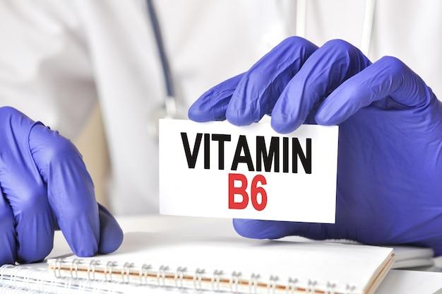 Mani del medico in guanti blu che tengono una carta con testo vitamina b6 sulla tavola di legno con lo stetoscopio