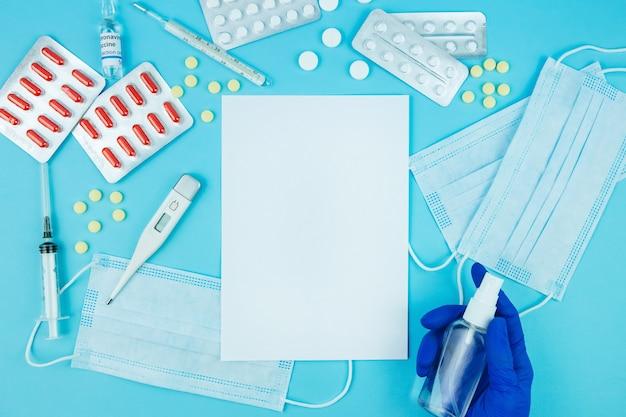 Mani del medico in guanti blu. medicina per coronavirus. medicinali nella lotta contro covid-19. pillole, siringhe, termometro, maschera medica sul tavolo blu. posto per il testo. vista dall'alto