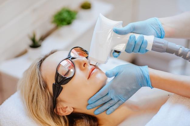 Mani del medico in guanti medicali blu utilizzando la macchina per la depilazione sul viso del paziente.