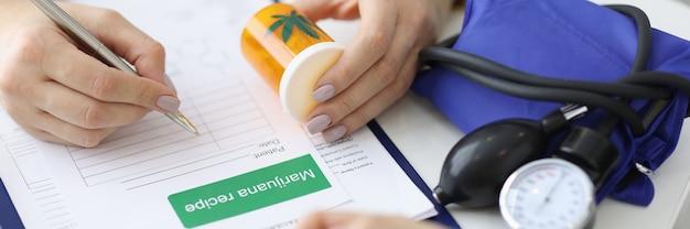 Le mani del dottore tengono la lattina di marijuana e scrivono la prescrizione. legalizzazione della marijuana per scopi medici concetto