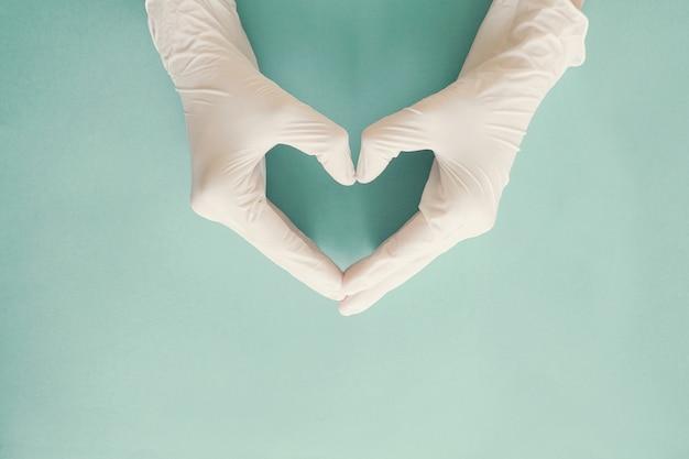 Mani del medico con guanti medicali a forma di cuore