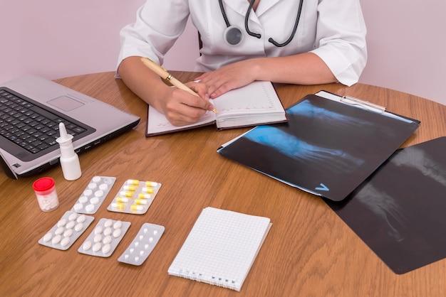 Mani del dottore con penna e taccuino andando a prendere appunti