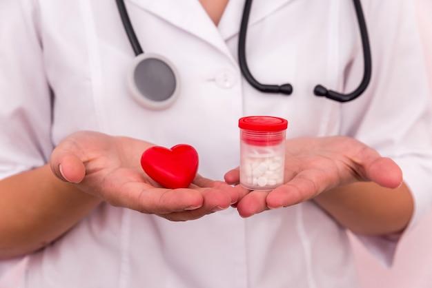 Mani del dottore con cuore rosso e pillole in contenitore