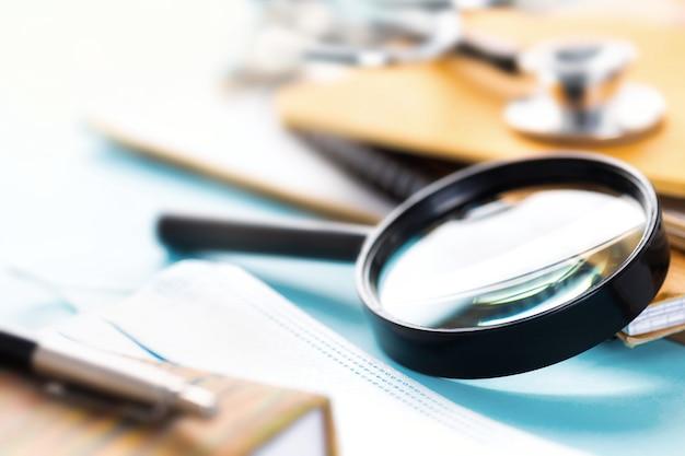 Posto di lavoro del medico con lente d'ingrandimento, stetoscopio o fonendoscopio, quaderni e documenti