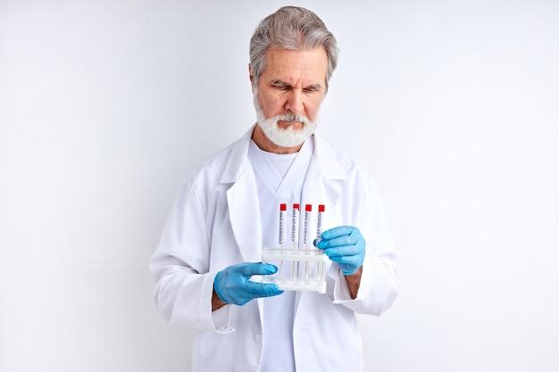 Il maschio dello scienziato medico tiene in mano il tubo del campione, esaminalo. medico con indumenti di protezione dal rischio biologico