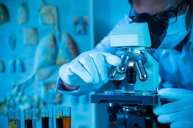 Il dottore o lo scienziato indossa una maschera medica e guarda al microscopio mentre lavora alla ricerca medica nel laboratorio covid-19 o del virus corona
