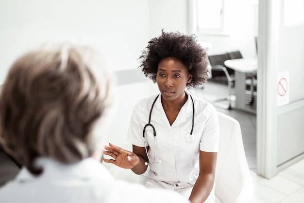 Medico e uomo anziano che comunica durante l'esame di referti medici in una sala d'attesa presso la clinica medica, ospedale.