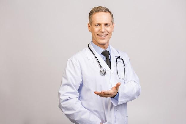 Aggiusti l'uomo senior, tenuta professionale medica qualcosa in mano vuota isolata sopra la parete grigia.