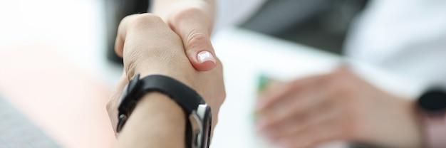 Medico che stringe la mano con il paziente in primo piano dell'ufficio