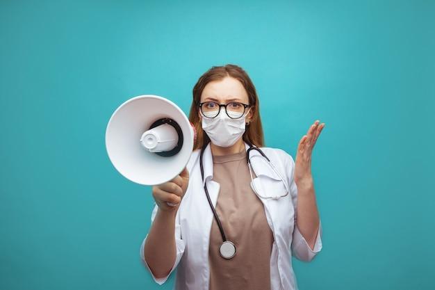 Medico che grida e urla sopra il megafono, operatore sanitario in dispositivi di protezione individuale che dà ordini al personale e ai pazienti in situazioni di emergenza.