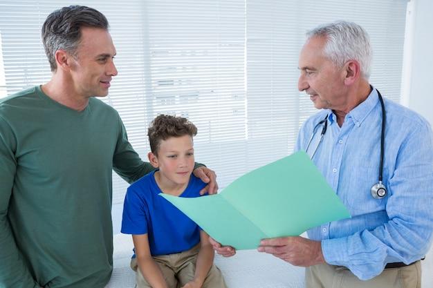 Medico che mostra referto medico al paziente e al suo genitore