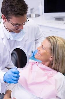 Medico che mostra specchio al paziente felice