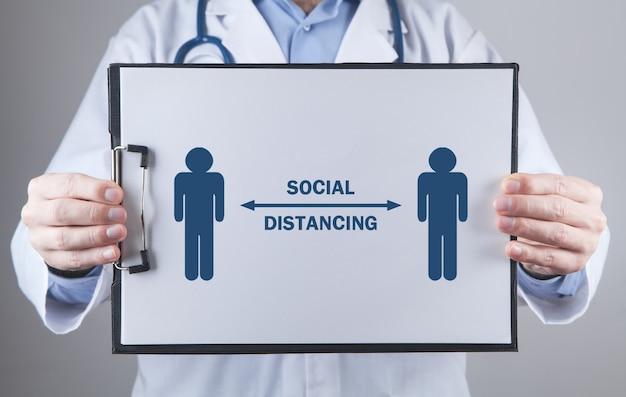 Medico che mostra il distanziamento sociale negli appunti. prevenzione del virus