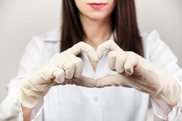 Il dottore mostra un cuore con le mani contro covid-19