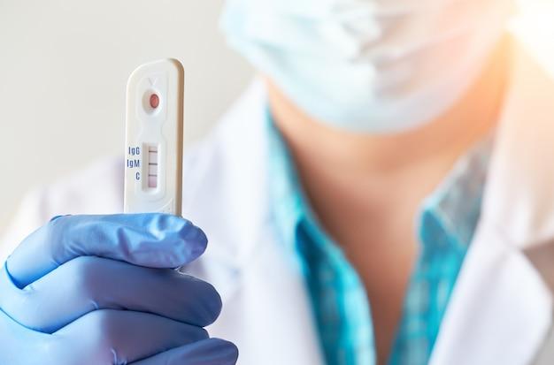 Il medico mostra un rapido test di laboratorio covid-19 per la rilevazione di anticorpi igm e igg contro il nuovo coronavirus, sars-cov-2 con esito positivo. immunità contro nuovi agenti patogeni che causano pandemie.