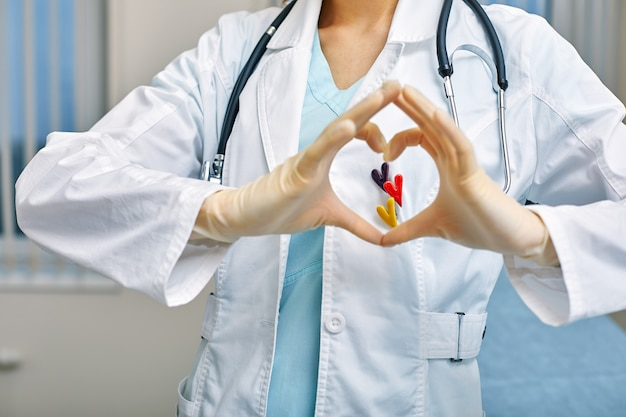 Medico mostra simboli di cuore attraverso le mani piegate a forma di cuore con il concetto di assistenza medica, medicina in ospedale, cardiologia.