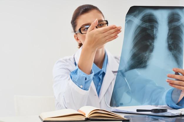 Il dottore si siede alla ricerca del radiologo dell'immagine dei raggi x del tavolo