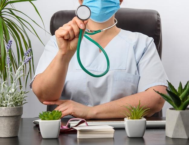Medico seduto a un tavolo nero in uniforme blu, specialista tiene in mano uno stetoscopio