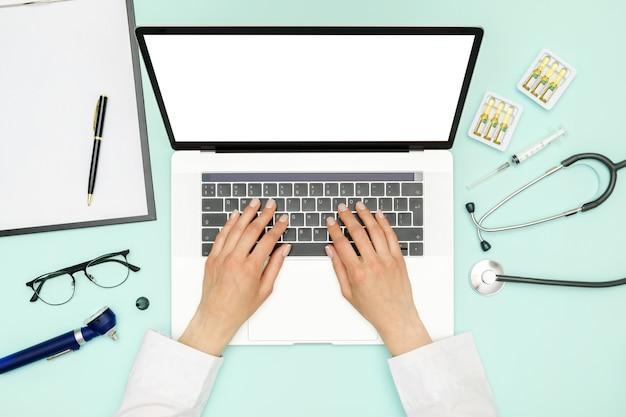 Medico che si siede alla scrivania blu e al lavoro