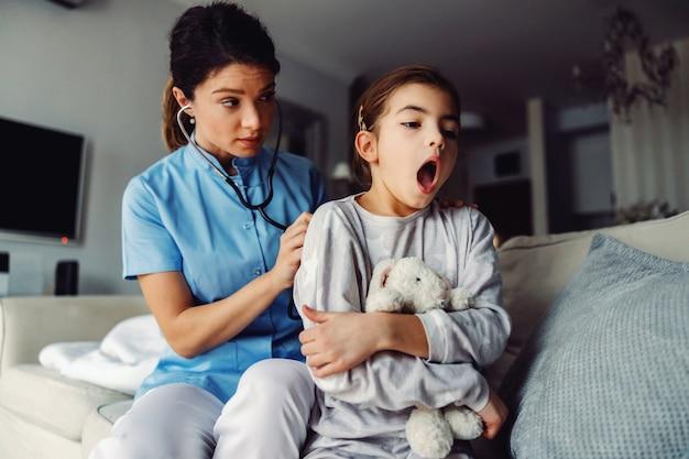 Dottore seduto sul divano accanto alla ragazza ed esaminando i suoi polmoni con lo stetoscopio.