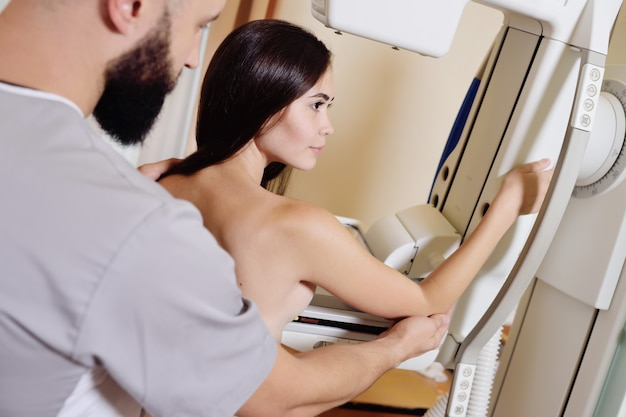 Dottore standing assisting patient undergoing mammogram x-ray tes